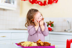 Little girl baking gingerbread cookies on Christmas Royalty Free Stock Photo