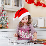 Little girl baking gingerbread cookies in domestic kitchen Stock Photography