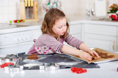 Little girl baking gingerbread cookies in domestic kitchen Stock Photo