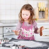 Little girl baking gingerbread cookies in domestic kitchen Royalty Free Stock Photos