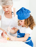 A little girl  baking with her grandmother Stock Photo