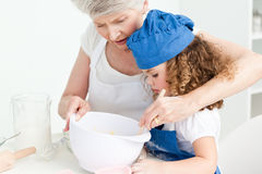 A little girl  baking with her grandmother Stock Images