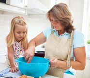 Little girl baking with her grandmother at home Royalty Free Stock Image