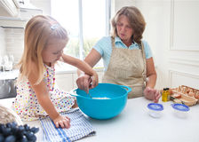 Little girl baking with her grandmother at home Stock Image