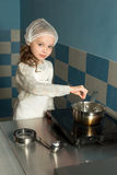 Little girl baking in the kitchen Stock Images