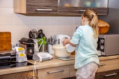 Little girl baking waffles in the kitchen following a recipe on the smartphone stock images