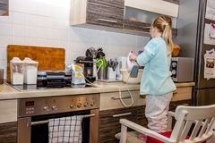 Little girl baking waffles in the kitchen following a recipe on the smartphone while standing on a chair. Little girl baking waffles in the kitchen at home royalty free stock photo