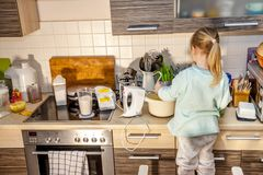 Little girl baking waffles in the kitchen following a recipe on the smartphone while standing on a chair. Little girl baking waffles in the kitchen at home stock images