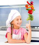 Little girl balanced pyramid of vegetables Stock Photography
