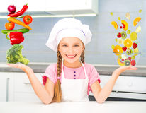 Little girl  balanced pyramid of vegetables and fruits Stock Photos
