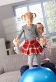 Little girl balancing on fit ball father helping Stock Image