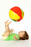 Little girl with a ball. A little girl throws feet a ball up Royalty Free Stock Image