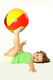 Little girl with a ball. A little girl holds feet a ball Royalty Free Stock Photo