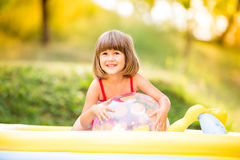 Little girl with ball in the garden swimming pool. Royalty Free Stock Photos