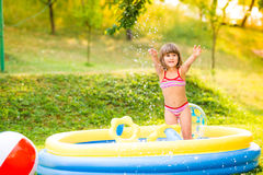 Little girl with ball in the garden swimming pool. Royalty Free Stock Image