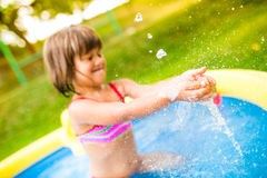 Little girl with ball in the garden swimming pool. Stock Image