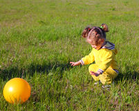 Little girl with ball on meadow Stock Image