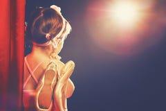 Little girl ballerina ballet dancer on stage in red side scenes Stock Photos