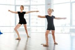 Little girl ballerina dancing with teacher in dance studio royalty free stock images