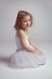 Little girl - ballerina tired and sitting on the floor Stock Photo