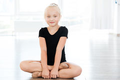 Little girl ballerina sitting with legs crossed in ballet studio. Portrait of happy beautiful little girl ballerina sitting with legs crossed in ballet studio Royalty Free Stock Photo