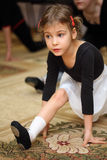 Little girl in ballet class sits on string. On floor with carpet royalty free stock photo