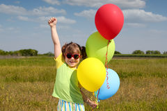 Little girl with balloons Stock Photos