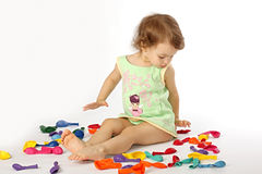 Little girl and balloons. A little girl sits in the coloured balloons Stock Images