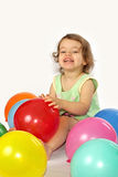 Little girl and balloons. A little girl sits in the coloured balloons Stock Photos