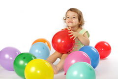 Little girl and balloons. A little girl sits in the coloured balloons Royalty Free Stock Image