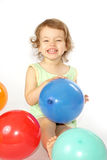 Little girl and balloons. A little girl sits in the coloured balloons Stock Image