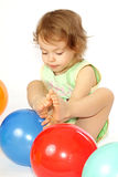 Little girl and balloons. A little girl sits in the coloured balloons Royalty Free Stock Photography