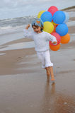 Little girl  with balloons on the beach. Little girl playing with balloons on the beach Stock Photography