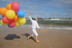 Little girl  with balloons on the beach Stock Photos