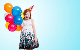 Little girl with balloons on blue background Royalty Free Stock Photography