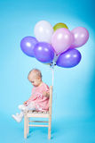 Little girl with balloons on blue background Royalty Free Stock Photos