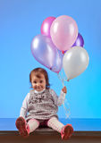 Little girl with balloons on a blue background Royalty Free Stock Image