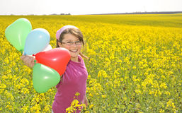 Little girl with balloons on field Stock Images