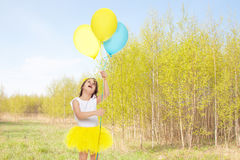 Little girl with balloons in his hands . Stock Photo