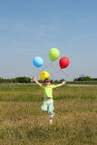 Little girl with balloons jumping on field Royalty Free Stock Photos