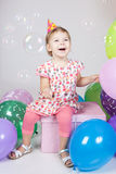 Little girl with balloons sitting on the gift Royalty Free Stock Photos