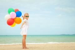 Little girl with balloons standing on the beach Royalty Free Stock Photo