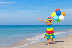 Little girl with balloons standing on the beach Stock Image