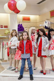Little girl with balloons stands with mannequins royalty free stock photo