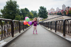 Little girl with baloons in the park Stock Photos