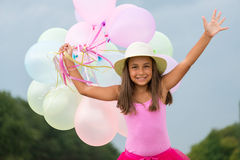 Little girl with baloons. Little girl running with balloons in her hand Royalty Free Stock Images