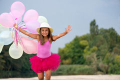 Little girl with baloons. Little girl running with balloons in her hand Royalty Free Stock Photography