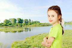 Little girl on a bank of the river Stock Photography