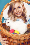 Little girl with basket with color eggs and white Easter bunny Stock Photo