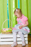Little girl with basket with Easter eggs Stock Photos